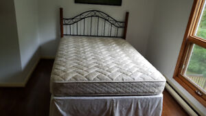 Queen size bed complete with Headboard, mattress, and cover