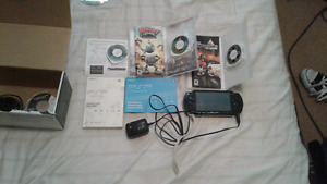 A black Playstation Portable with 3 games, charger included