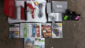 Red Nintendo Wii with a few games