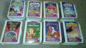8 Disney action figures in boxes that look like small vhs tapes