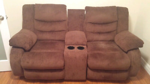 Reclining love seat with center storage and drink holder