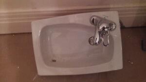 Lavabo rectangulaire avec robinet en coin.