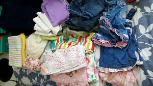 Assorted baby girl clothes and blankets