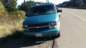 Blue Chevrolet van, matress, camping gear