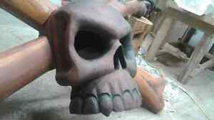 Chainsaw carving skull and crossed bones
