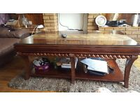 Dark brown solid oak coffee table with underneath shelve and glass top