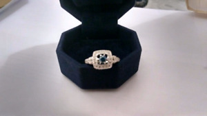 14 k white gold ring with beautiful blue diamond in the centre.