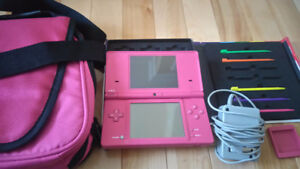 Pink Nintendo DSi with a bunch of accessories and charger