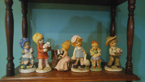 For sale porcelain figurines of boys and girls and wooden racks