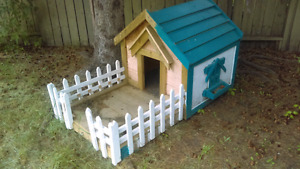 Nice little dog house with white picket fence half painted