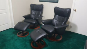 Two black recliners with foot rests