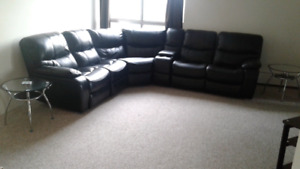 Large black sectional couch with tables