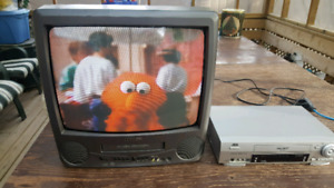 TV/VCR combo and VCR with box of videos.