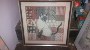 framed needlepoint work of a siamese cat