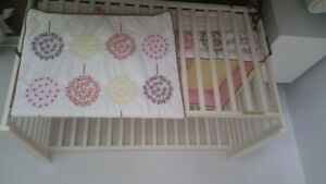 Baby crib and bedding in white.