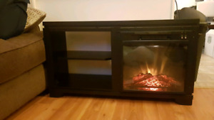 Tv stand with lighted electric fireplace.