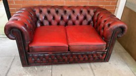 A Red Leather Chesterfield Two Seater Sofa