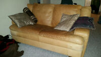 Leather Sofa with complimentary throw pillows and fabric cover