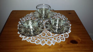 silver-plated tea-cups and saucers.