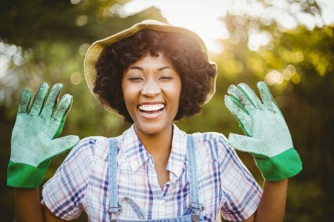 smiling woman holding up gloved hands