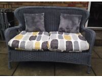 Grey wicker sofa. Garden or conservatory.