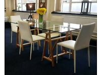 Solid glass top dining table with adjustable height wooden legs, and 4 white leather dining chairs