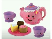 Toy tea set and wooden table top kitchen