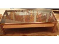 Used Retro smoked glass top wooden coffee table with wooden shelf.