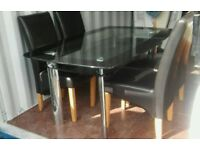 Glass dining table with 4 chairs. Can deliver