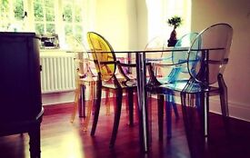 Glass and chrome dining table and 6 Philip stark coloured ghost chairs in differing colours