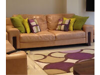 Real leather sofas 2x4 seaters with solid wooden feet in a tan colour
