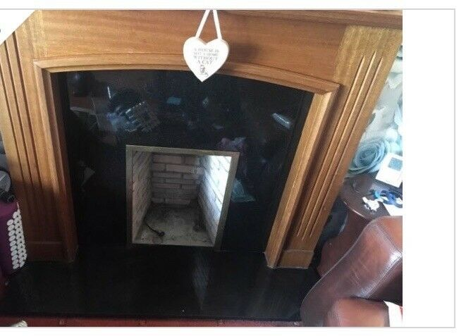Black marble fire place with oak wood surrounding