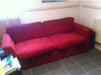 Comfortable red sofa available for collection.