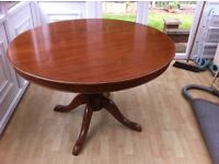 Dining table 118cm round extending 156cm oval. Dark wood on a central pedestal.