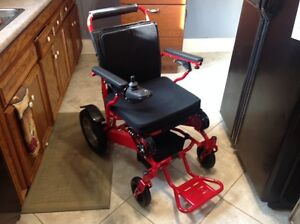 Red electric wheelchair that folds for transportation