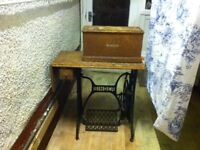 VINTAGE SINGER SEWING MACHINE- In working condition with an electric motor & on wrought iron table.