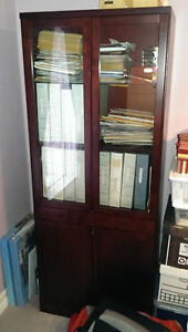 Wood shelving unit with glass top doors.
