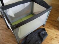 grey with green travel cot.