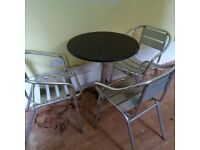 small black granite garden or patio table with three aluminium chairs can deliver