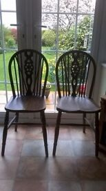 Two matching wooden chairs both have slight wooble