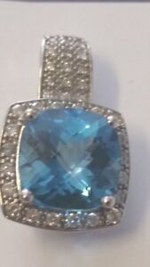 6.46 TDW Blue Topaz surrounded by 35 Diamonds, pendant.