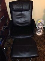Black leather chair and ottoman chair swivels.