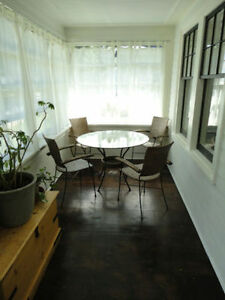 Dining set glass top and four wicker/ cast iron chairs.