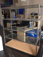 Glass commercial shelving unit on wheels