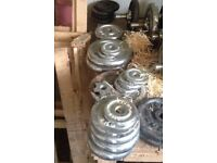 Collection of free weights in various sizes including bar