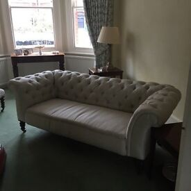 Antique roomy chesterfield sofa upholstered in pale stone silk with drop arm