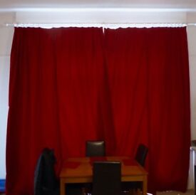 Sumptuous extra large red curtains with cream lining.