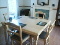 Solid dining room table (4 foot by 3.5 foot) and 4 dining chairs for sale.
