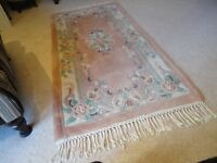 Chinese rug, pure wool, oblong, pink floral background, with fringe.