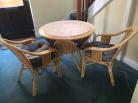 Cane round table with 2 chairs and cushions